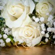 Gold wedding rings on a bunch of flowers for the bride — Stock Photo