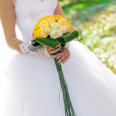 Wedding bouquet from fresh flowers in hands of the bride. — Stock Photo
