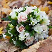 The wedding bunch of flowers lies on fallen leaves. — Stock Photo