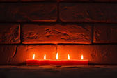 Burning candles are on the old stone surface. — Stock Photo