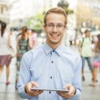Young smiling man with tablet computer on street — Stock Photo
