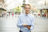 Goodlooking men with tablet computer on urban street — Stock Photo