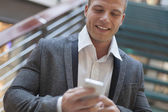 Businessman read good news on smartphone, business building inte — Stock Photo