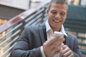Happy businessman with smartphone in business building — Stock Photo