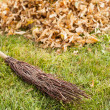 Autumn clearing - besom and a pile of leaves — ストック写真
