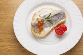 Sandwich with herring fish and caviar on bread, cherry tomato — Stok fotoğraf