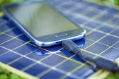 Charging smart-phone with solar charger — Stock Photo