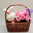 Pink roses in a basket and white rabbit toy — Stock Photo