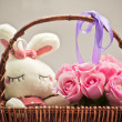 Pink roses in a basket and white rabbit toy — Stok fotoğraf