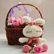 Pink roses in a basket and white rabbit toy — Zdjęcie stockowe
