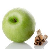 Ripe green apple with cinnamon sticks — Stock Photo