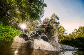 Quad rider through water stream — Stock Photo