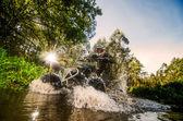 Quad rider through water stream — Stock Photo