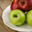 Apples in a ceramic white plate — Stock Photo