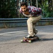 Stock Photo: Downhill skateboarder in action