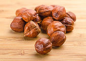 A pile of shell-less hazelnuts, isolated on textural wood backgr — Stock Photo
