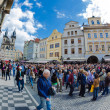 Tourists walk around the Old Town Square in Prague waiting for s — Stockfoto