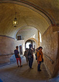 Tourists walk along the corridors of a medieval castle — Stock Photo