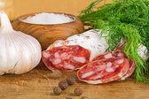 Dilimlenmiş salame üzerinde kesme tahtası, dereotu, biber, tuz — Stok fotoğraf