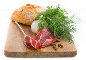 Rustic still life with bacon, bread, garlic and herbs — Stock Photo