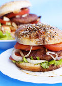 Burger with meat and baked vegetables on a blue background — Stock Photo