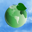 Ecology concept.Green planet on a blue sky - Stock Photo
