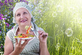 Adult female eating fresh vegetable salad on a nature — Stock Photo
