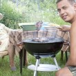 Happy family preparing a barbecue in the summer garden — Stock Photo