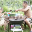 Stock Photo: Happy family preparing a barbecue in the summer garden
