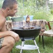 Adult man preparing a barbecue in the summer garden — Stock Photo