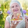 An elderly woman eats vegetable salad on background of meadow flowers — Stock Photo