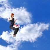 Happy red-haired girl with gifts and a phone in cloud dreams on a chair — Stock Photo