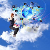 Happy red-haired girl with gifts and a phone in cloud dreams on chair.Internet shopping — Stock Photo