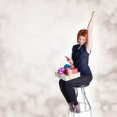 Happy red-haired girl with gifts and phone on a chair at a festive abstract background — Stock Photo