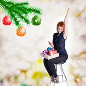 Happy red-haired girl with gifts and phone on a chair.Holidays Christmas and New Year — Stock Photo