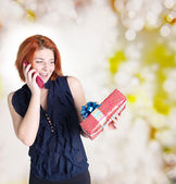 Happy woman with a phone and a gift box.Holiday concept — Stock Photo