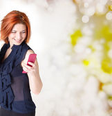 Emotional happy woman with red hair and a telephone on the abstract festive background — Stock Photo
