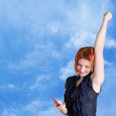 Connect.Happy red-haired girl with mobile phone on a blue sky background. — Stock Photo