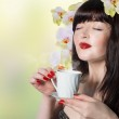 Best tradition tea.Beautiful girl with a cup of green tea buds of orchids — Stock Photo #38230515