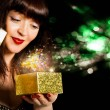 Stock Photo: Beautiful Girl opens gift in small box golden festive night.Holiday
