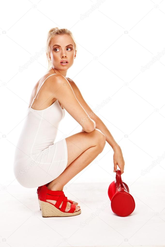 Trendy attractive blonde woman in a short white summer dress squatting on the floor wearing red sandals and bag  Stock Photo #12657489