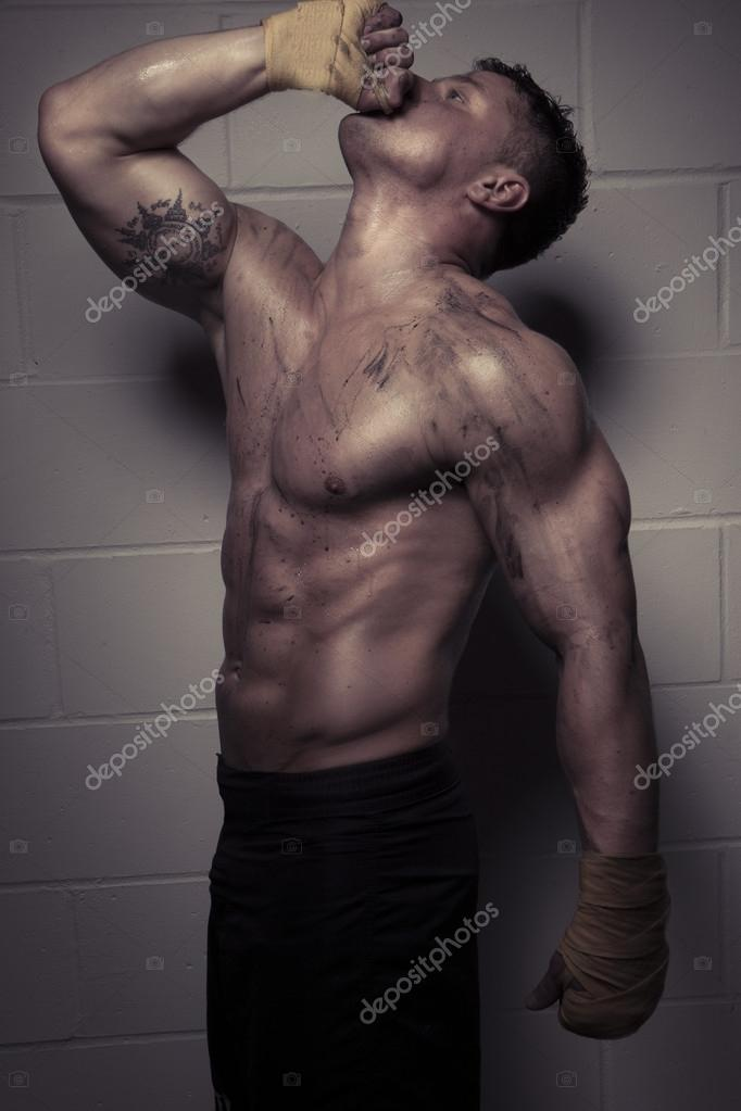 Dark portrait against a tiled wall of a sexy macho handsome bodybuilder with muscular physique stretching upwards with his hand to his mouth — Stock Photo #13373432