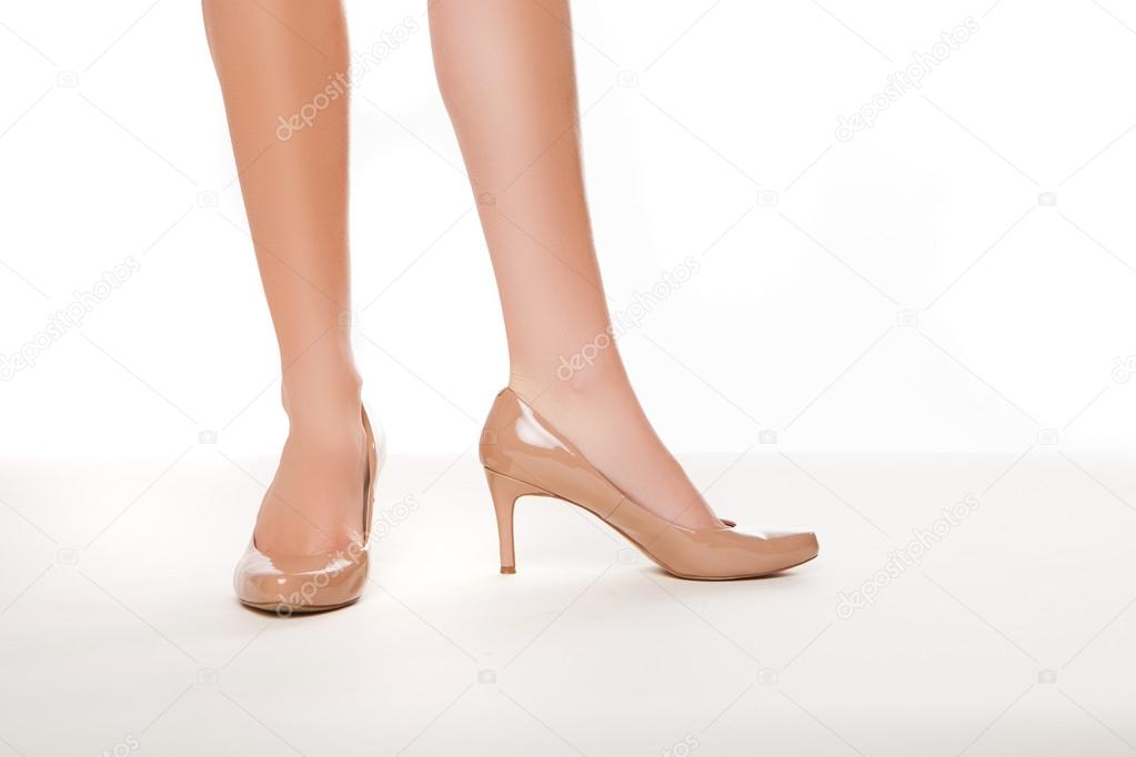 Cropped view image of the shapely legs of a woman in stylish simple high heeled shoes on a white background — Stock Photo #13619867