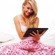 Girl using a tablet on her bed — Stock Photo