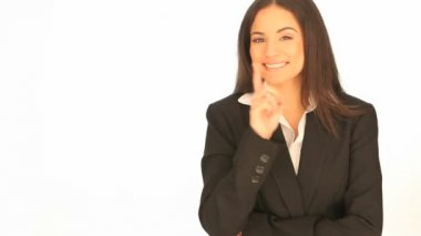 Beautiful brunette laughing businesswoman pointing to the side of the frame with her finger towards blank copyspace