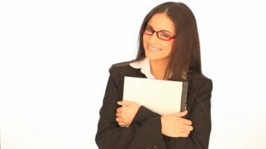 Beautiful smiling businesswoman wearing glasses holding a laptop to her chest against a white studio background