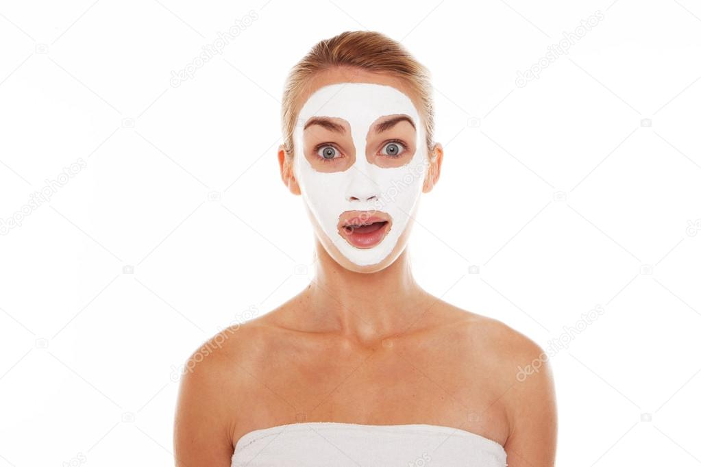 Beautiful blonde woman in face mask and towel with a surprised wide eyed expression isolated on white — Stock Photo #13636553