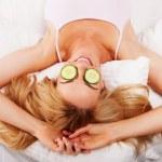 Woman using cucumber eyepads — Stock Photo #13652378
