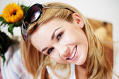 Smiling woman with sunglasses on her hair — Stock Photo