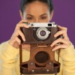 Woman holding a vintage film camera — Stock Photo